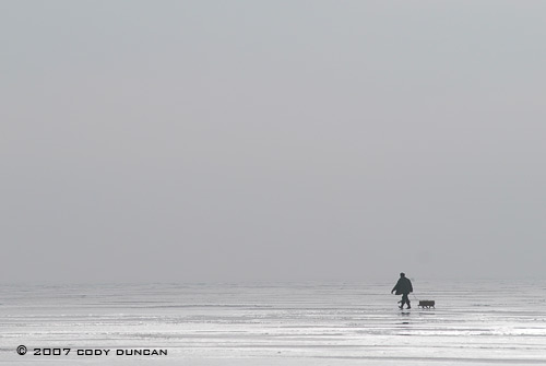 © cody duncan photography. Ice fisherman walking on frozen curonian lagoon, lithuania