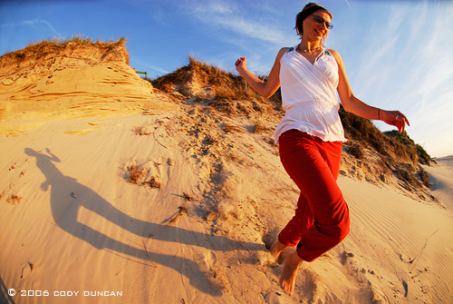 woman running down sand dune on Island of Juist, Germany. © Cody Duncan Photography