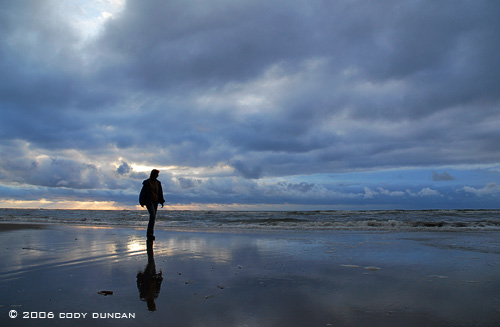 woman walking along shore of North sea at sunset on the island of Juist, Germany. © Cody Duncan photography