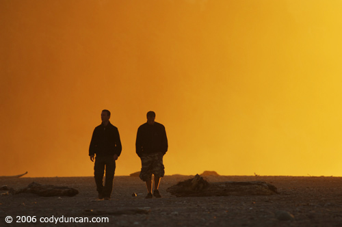 New Zealand, two people walking along Okarito beach at sunset.  © Cody Duncan Photography
