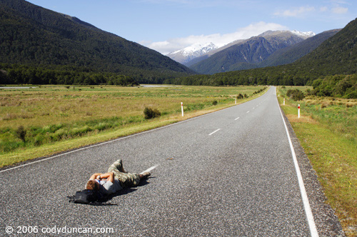 New Zealand travel photography: person lying in empty road near Haast Pass. © Cody Duncan Photography