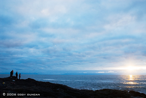 Group of people waiting to view the midnight sun along coast in Lofoten Islands, Norway. © Cody Duncan Photography