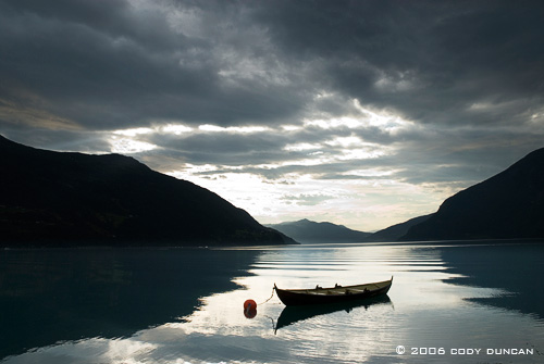 Reflection of small boat in Norwegian Fjord. © Cody Duncan Photography