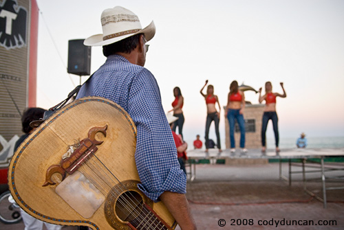 2008 Baja 250 San Felipe. Street musician watching women dancers during pre-race festival.  © Cody Duncan Photography