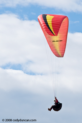 Paraglider flying in air with cloudy sky, Germany. Cody Duncan travel stock photography