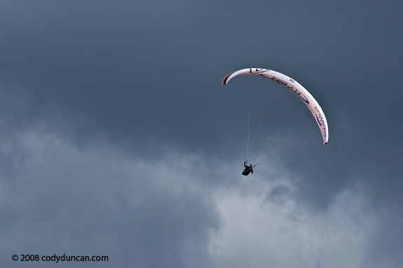 Paraglider flying in air with stormy sky, Germany. Cody Duncan travel stock photography