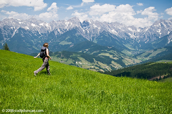 Female hiker crossing mountain meadow with Austrian alps in background, Maria Alm, Austria. © Cody Duncan photography