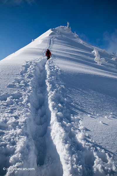 Adventure stock photo: Woman hiking in deep snow towards summit of Jenner, Berchtesgaden national park, Bavaria, Germany. Cody Duncan Photography