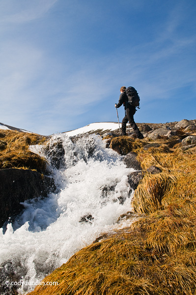 Travel stock photography: Female backpacker hikes near running river in cairngorm mountains, Scotland