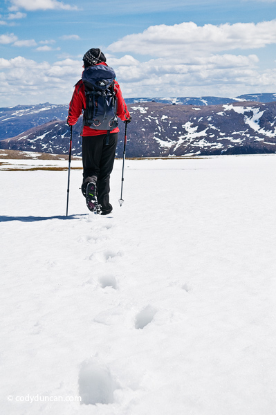 Adventure stock photography: Female hiker crosses snowfield near summit of Cairn Lochan in the Cairngorm mountains, Scotland