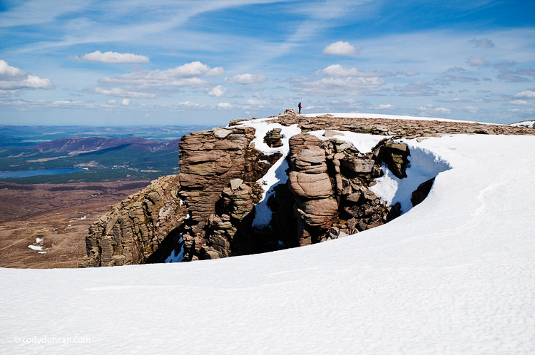 Travel stock photography: Person stands in distance on summit of Cairn Lochan in the Cairngorms, Scotland