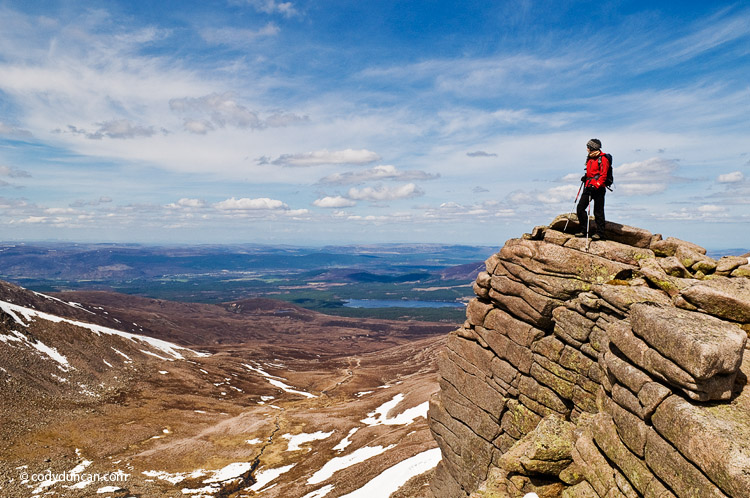 lifestyle stock travel photography: Female hiker stands on cliff near Cairn Gorm in the Cairngorm mountains of Scotland
