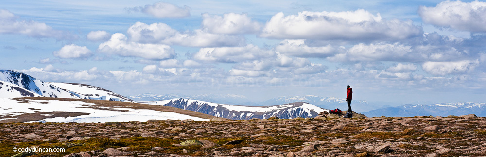 Panoramic stock photography: Female hiker takes in view of Cairngorm mountains from near summit of Cairn Lochan, Scotland