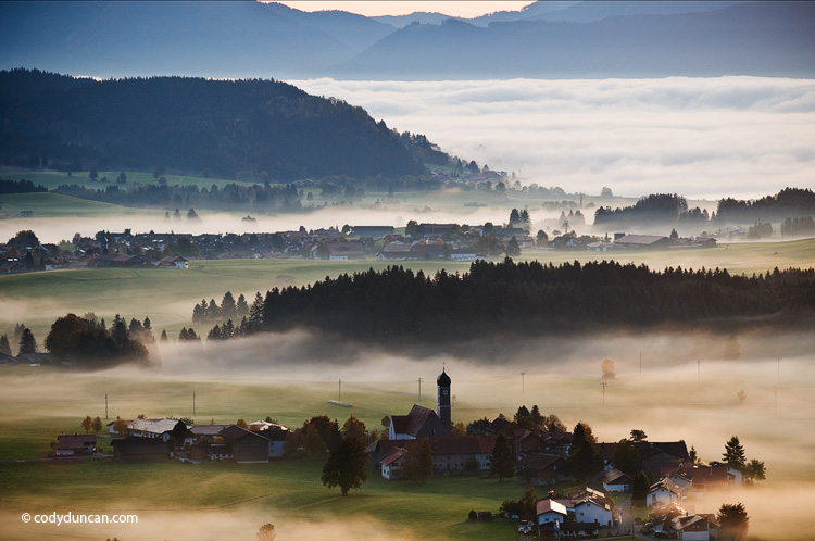 Autumn morning fog clears from village of Speiden and rural landscape of Allgaeu region, near Eisenberg, Bavaria, Germany