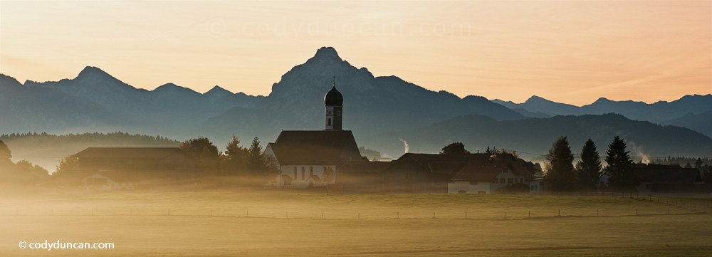 Wallfahrtskirche Maria Hilf  in the small village of Speiden with Early morning autumn mist and mountain peak SŠuling in distance, AllgaeŠu region, Bavaria, Germany