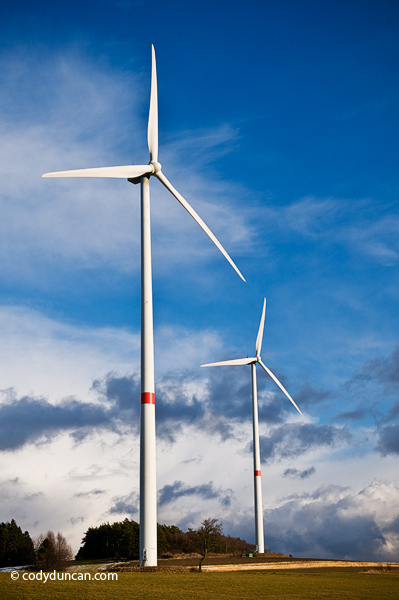 Alternative green energy production stock photo: Power generating wind turbines stand in farm field, Bavaria, Germany. Cody Duncan photography