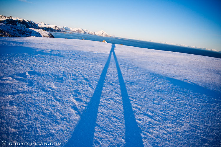 Lofoten islands winter mountain photo: shadow of hiker across snowy landscape