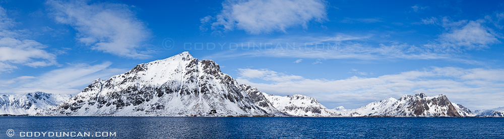 Justadtind and mountains of Vestvagoy rise from sea fjord, viewed from near Stamsund, Lofoten islands, Norway