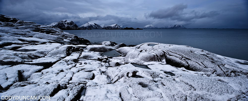 Lofoten islands panoramic landscape photography: Autumn snow covers rocky coastline