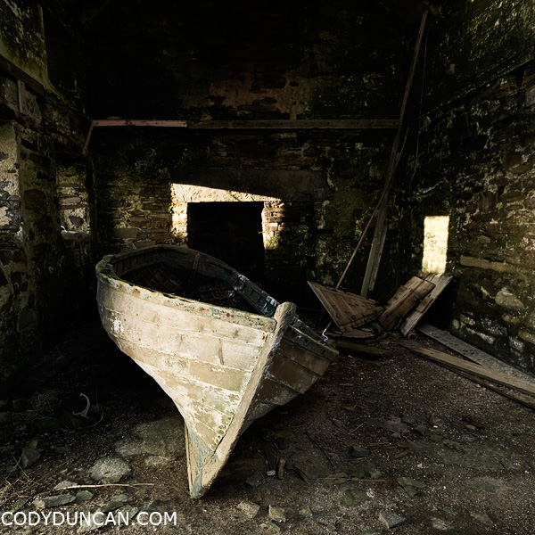 Orkney travel stock photograph - Old boat sits abandoned in Barn, South Ronaldsay, Orkney
