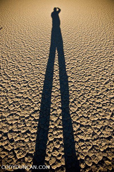 travel and landscape photographer Cody Duncan stands on dry lake bed at Racetrack playa, Death Valley, California