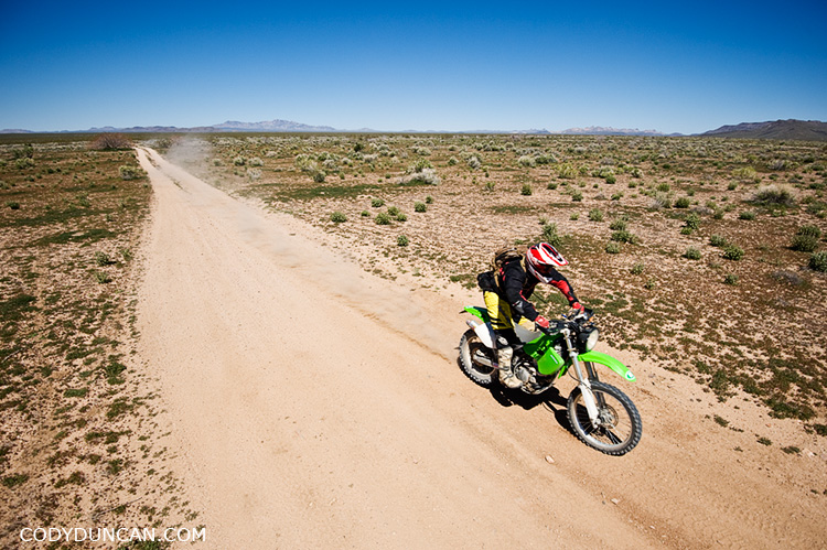 Dual sport motorcycle rides through desert along Mojave trail road, California