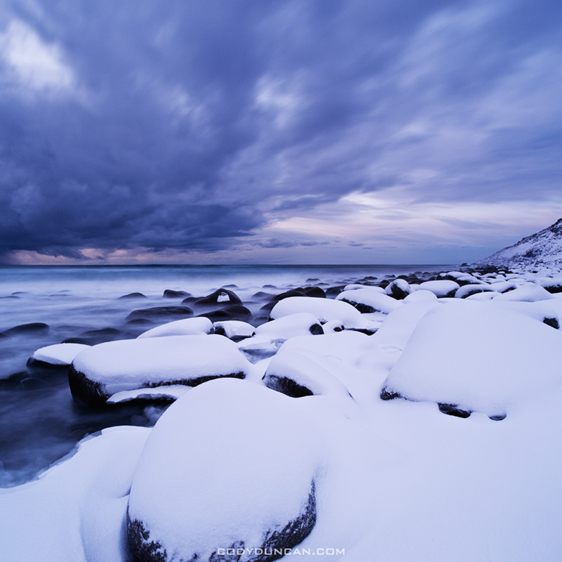 Snow covered rocks at Unstad beach, Lofoten islands, Norway