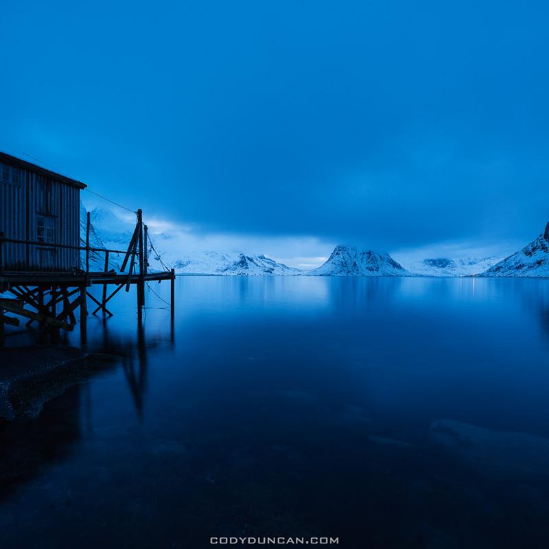 Rorbu sits on edge of fjord, Vestvalen, Reine, Moskenesøy, Lofoten Islands, Norway