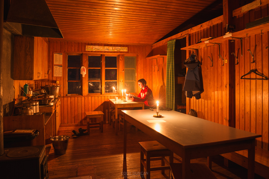 Candlelight illumintes room Singi mountain hut at night, Kungsleden trail, Lappland, Sweden