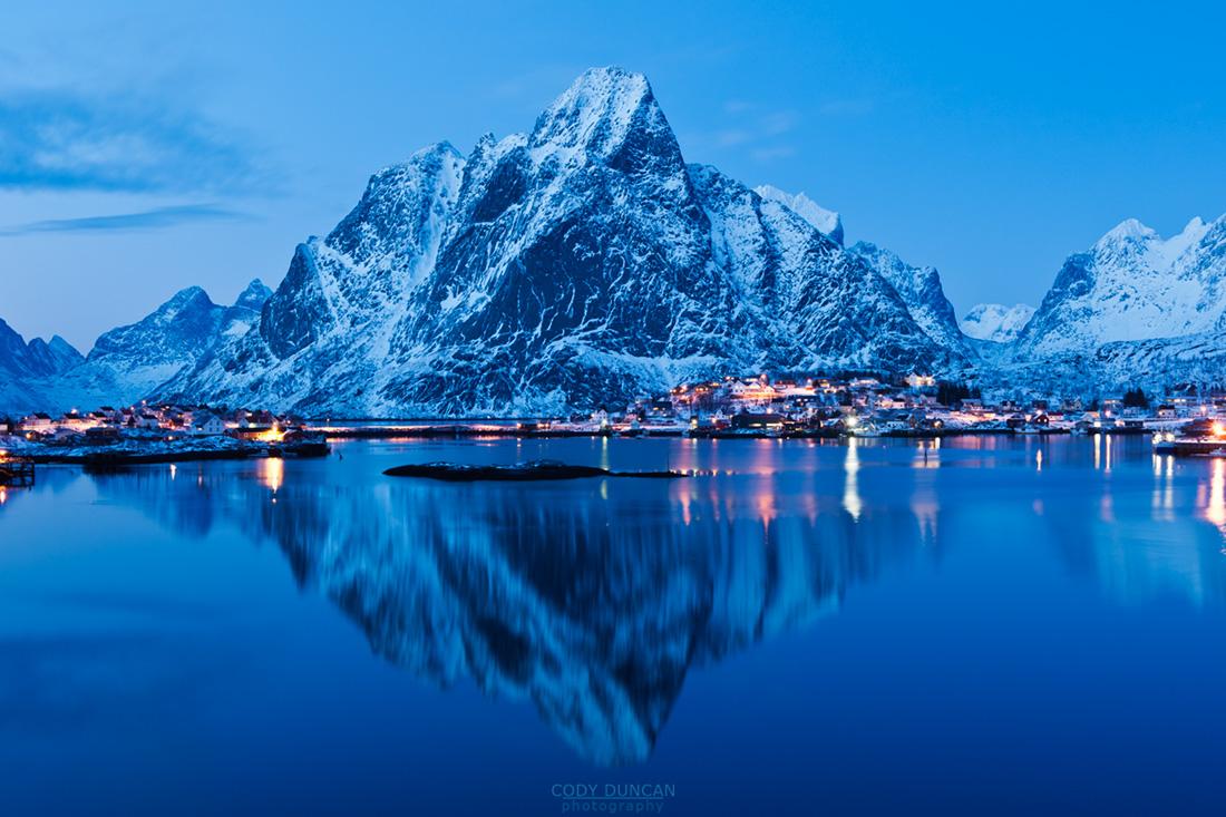 Reflection of Olstind mountain peak in harbour at Reine, Lofoten Islands, Norway