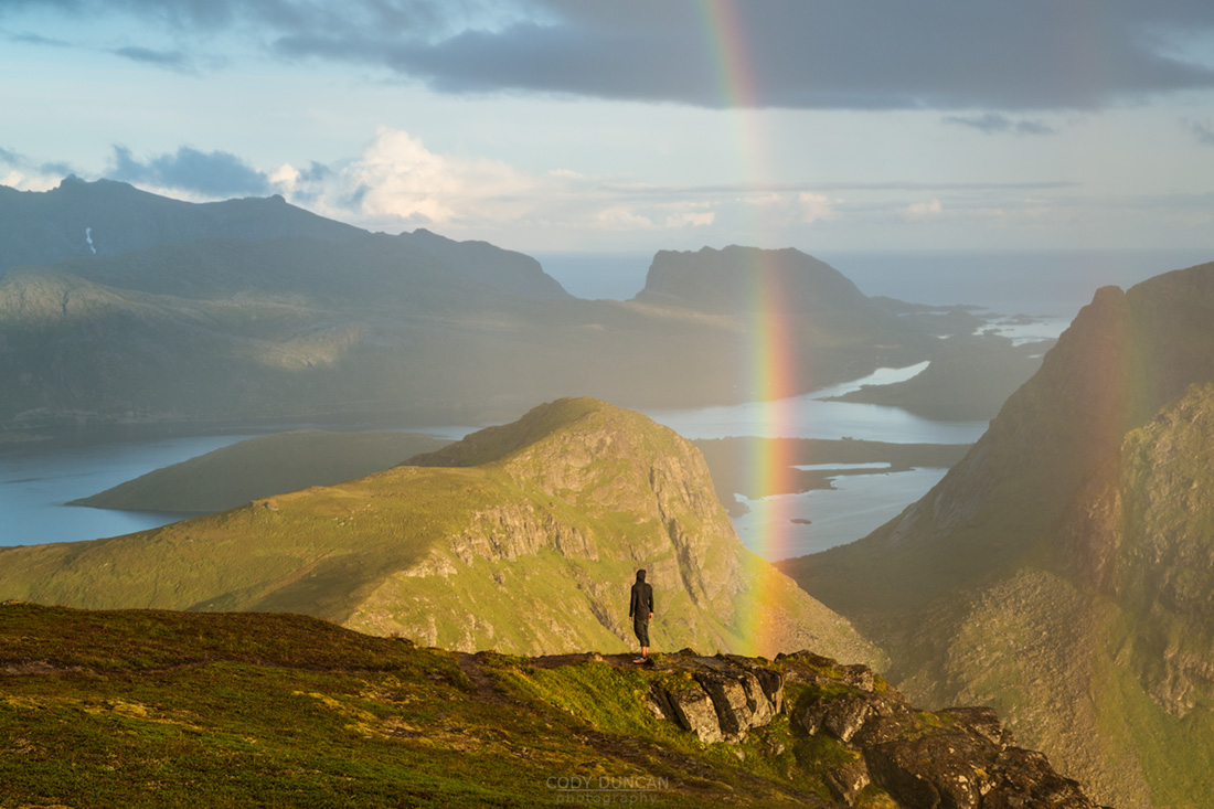 Person stands under rainbow near summit of Ryten, Lofoten Islands, Norway