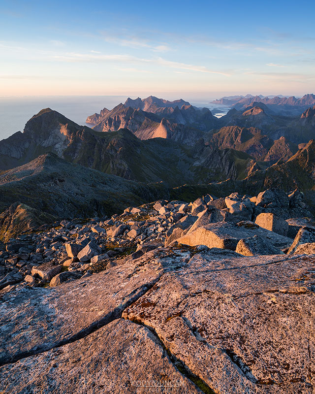 Evening light over mountain landscape from rocky summit of Hermannsdalstinden, Moskenesoy, Lofoten Islands, Norway