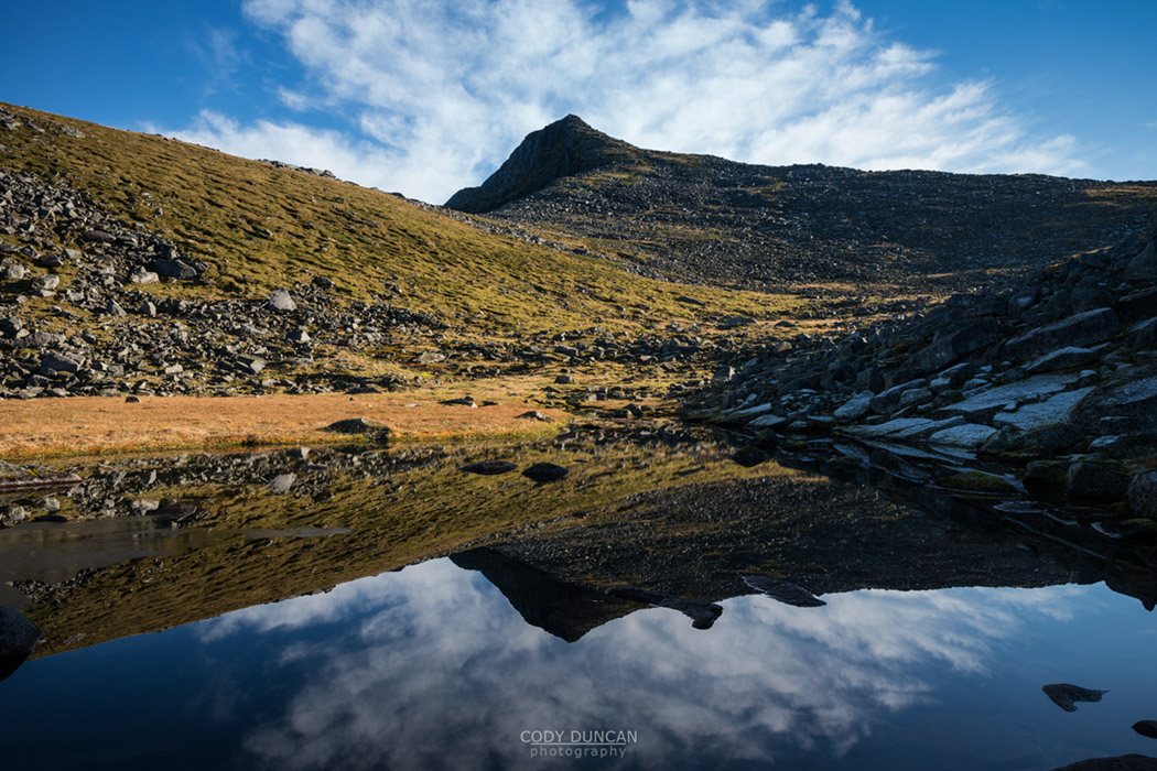 Kroktind (707m) mountain peak reflects in small lake, Austvagoy, Lofoten Islands, Norway