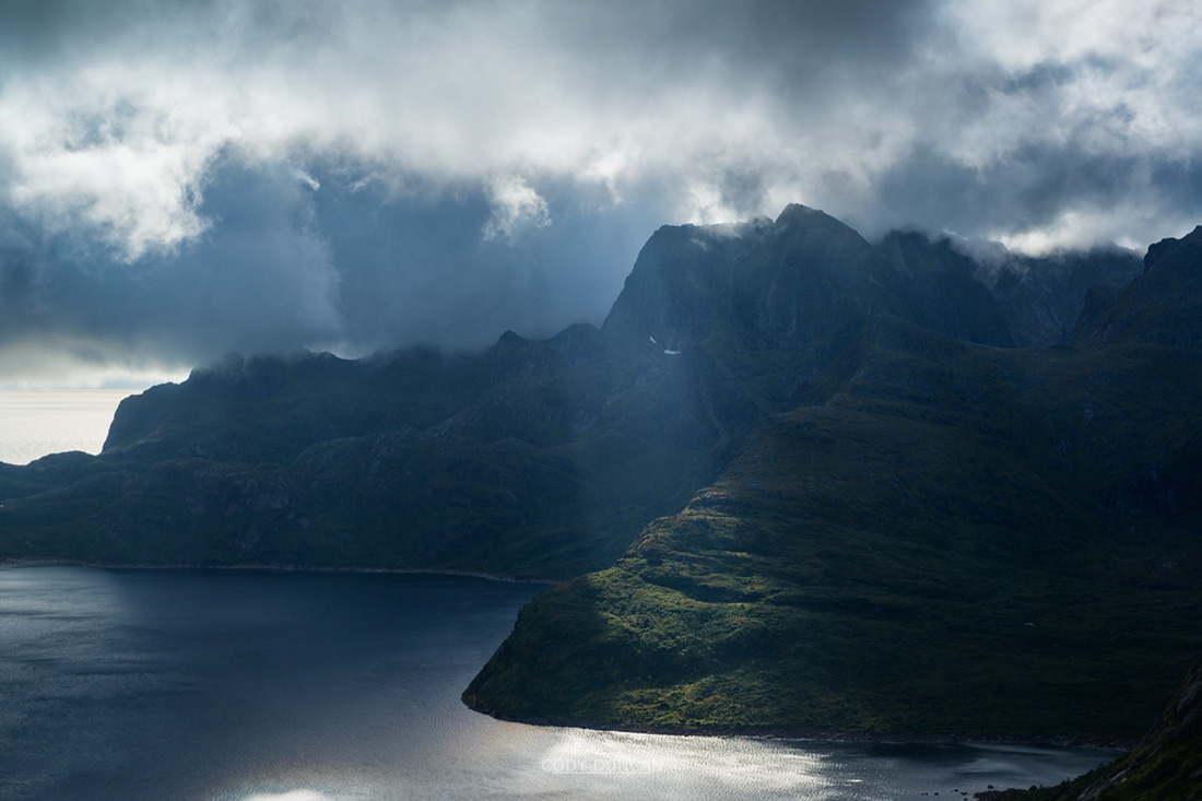 Sunlight pierces through clouds on Solbjørnvatnet, Moskenesoy, Lofoten Islands, Norway
