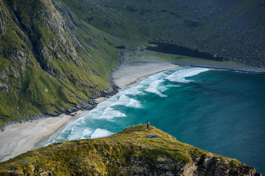 Female hiker overlooking Kvalvika beach from nearby mountain, Moskenesoy, Lofoten Islands, Norway
