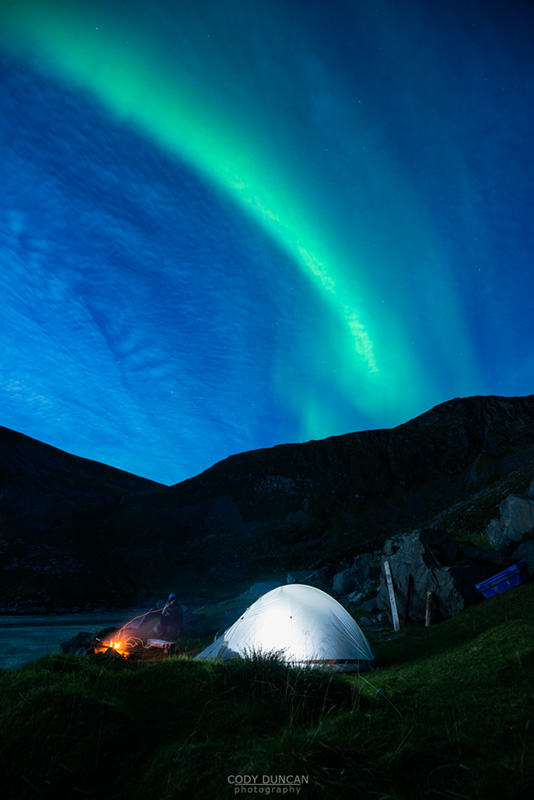 Illuminated tent with Northern Lights in sky at Kvalvika beach, Moskenesoy, Lofoten Islands, Norway