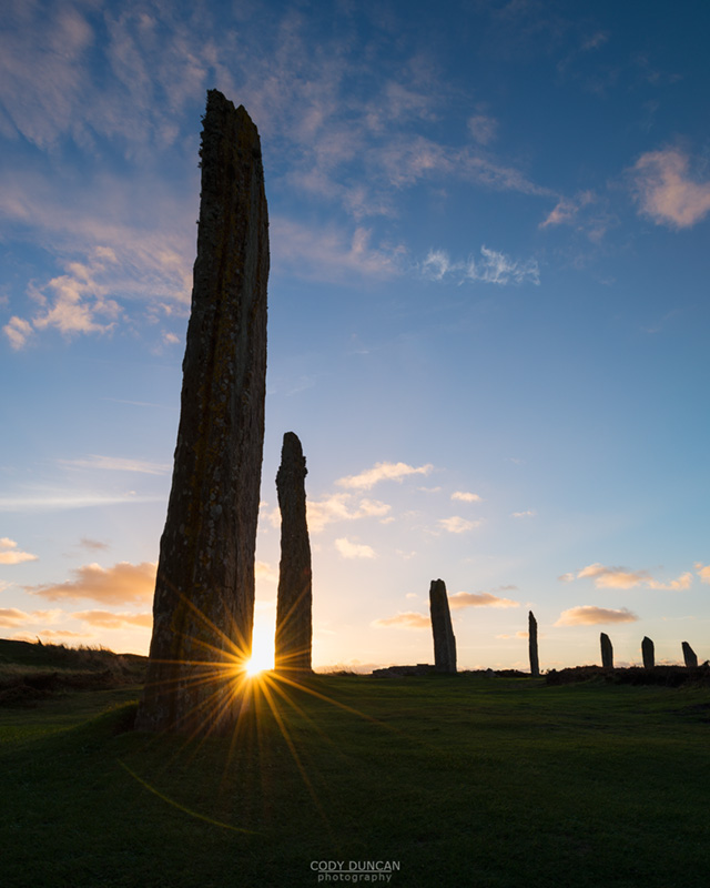 Setting sun shines behind standing stone at Ring of Brodgar, Orkney, Scotland