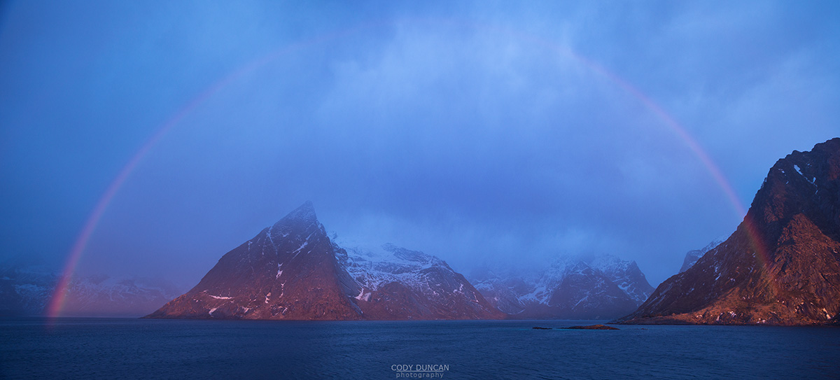 Rainbow forms over Olstind mountain peak and Fjord, Reine, Moskenesøy, Lofoten Islands, Norway