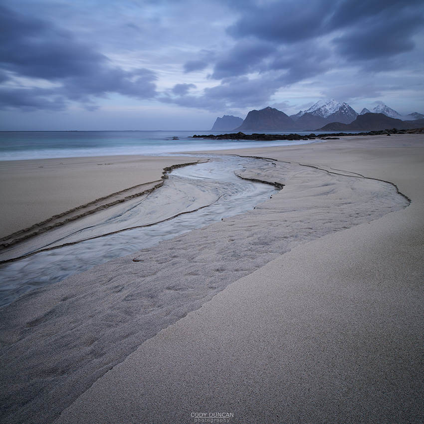 A small river runs through the sand at Storsandnes beach, Flakstadøy, Lofoten Islands, Norway