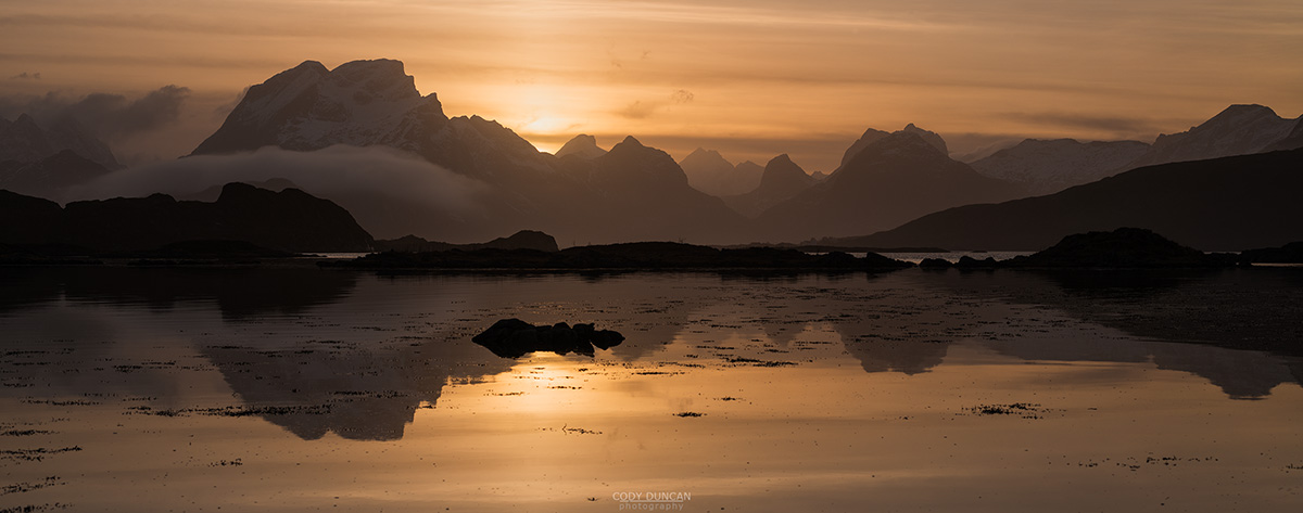 Mountains of Moskenesøy rise above sea at sunset, near Fredvang, Flakstadøy, Lofoten Islands, Norway