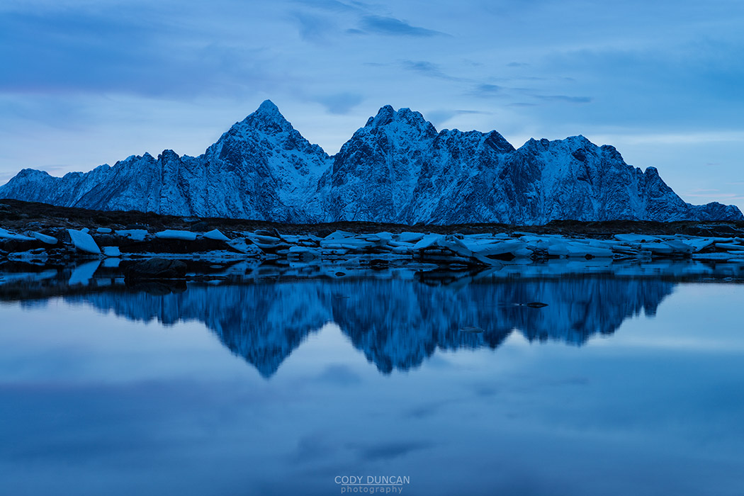 Reflection of Vågakallen mountain peak over coastline, Vestvågøy, Lofoten Islands, Norway