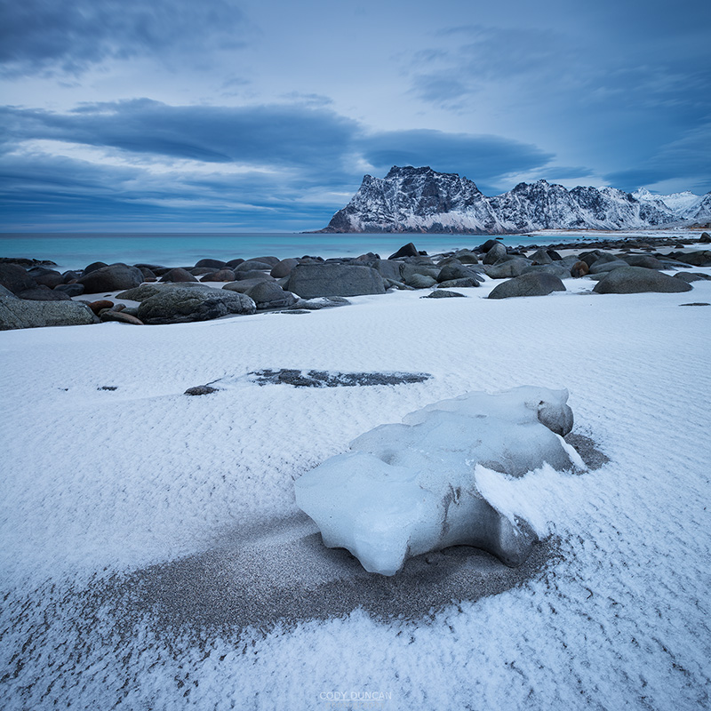 Dusting of snow covers sand at Uttakleiv beach, Vestvågøy, Lofoten Islands, Norway