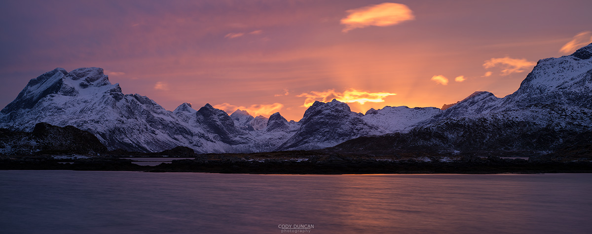 Colorful sunset over mountains of Moskenesøy, near Fredvang, Flakstadøy, Lofoten Islands, Norway