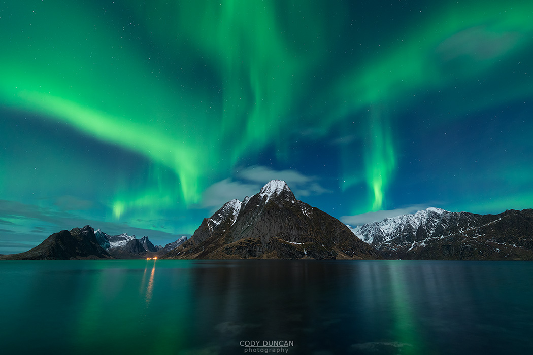 Northern Lights - Aurora Borealis shine in sky over Olstind mountain peak and fjord near Reine, Moskenesøy, Lofoten Islands, Norway