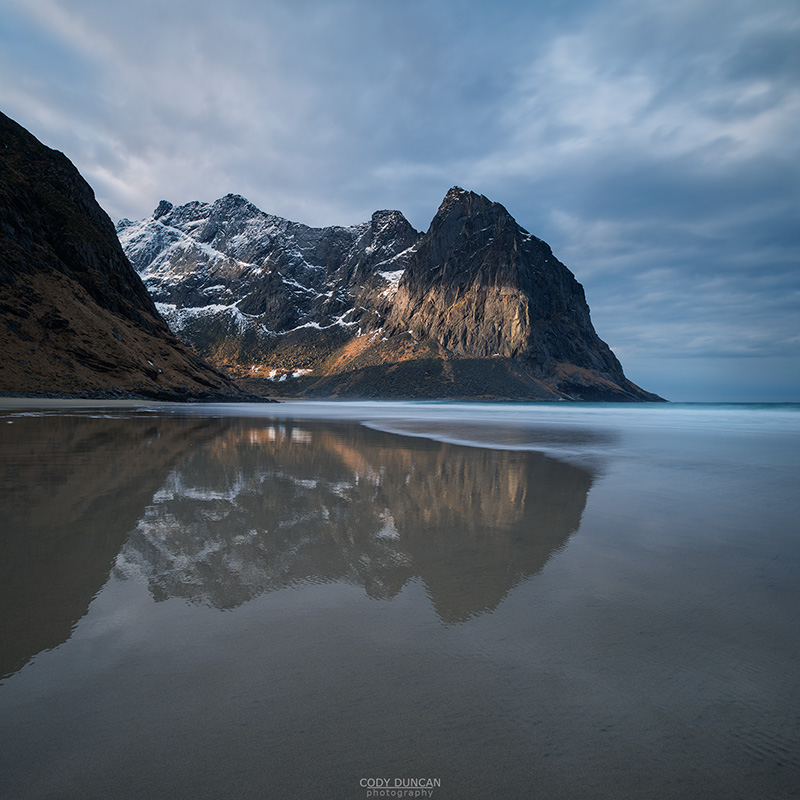 Mountain peaks rise over empty sands at Kvalvika beach, Moskenesøy, Lofoten Islands, Norway