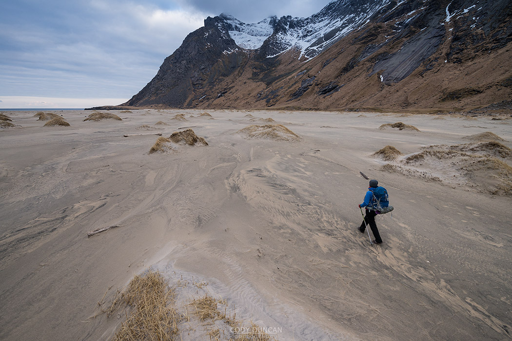 Female hiker hiking across sand at Horseid beach, Moskenesøy, Lofoten Islands, Norway