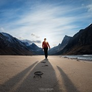 Female hiker leaves footprints in sand on scenic Horseid beach, Moskenesøy, Lofoten Islands, Norway