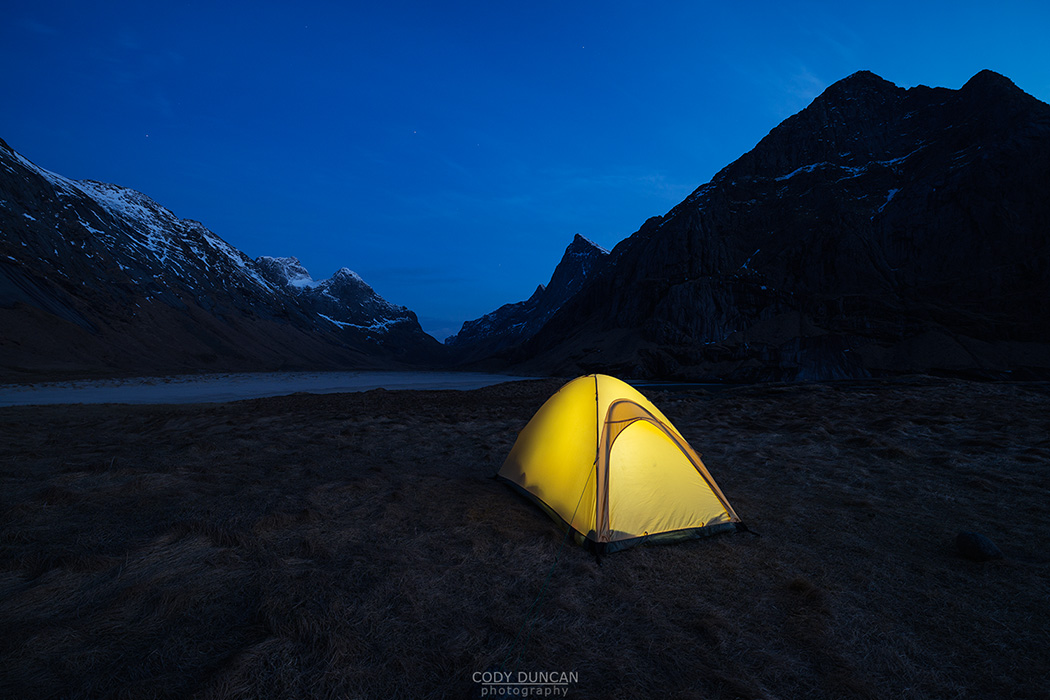 Tent illuminated at night while wild camping at scenic Horseid beach, Moskenesøy, Lofoten Islands, Norway