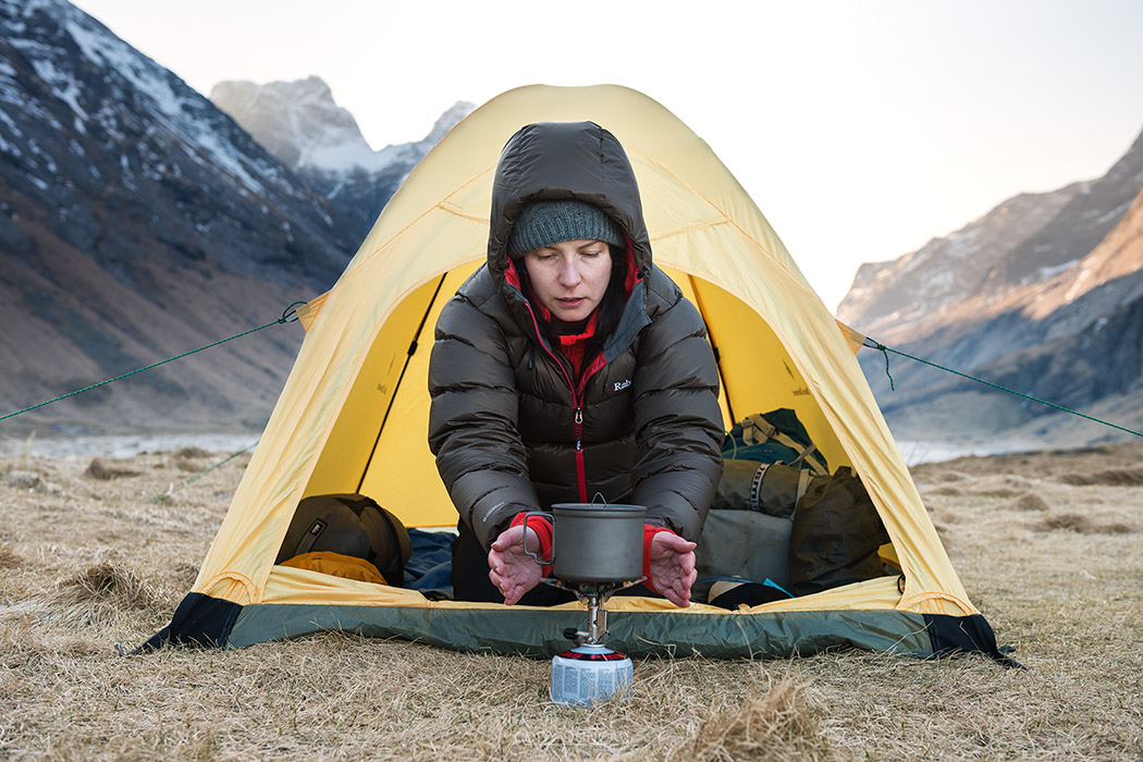 female hiker warms hands with stove on cold morning wild camping at Horseid beach, Moskenesøy, Lofoten Islands, Norway