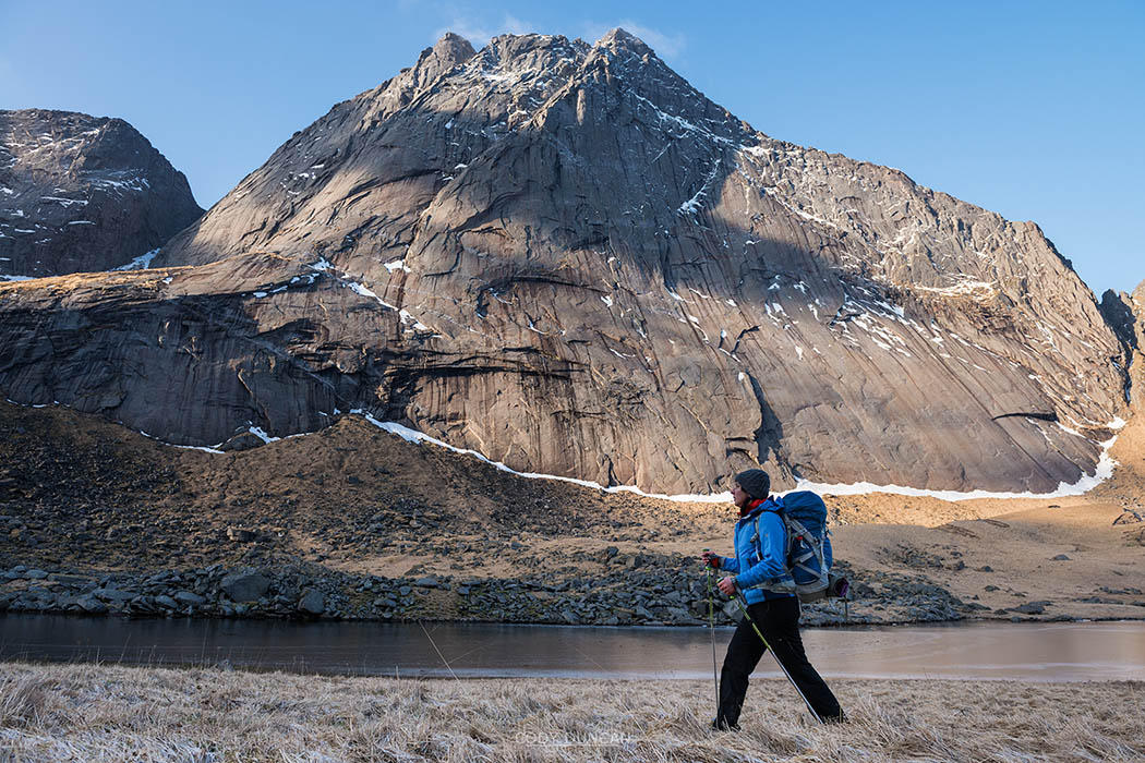 Mountain peak rises above female hiker hiking trail away from Horseid beach, Moskenesøy, Lofoten Islands, Norway